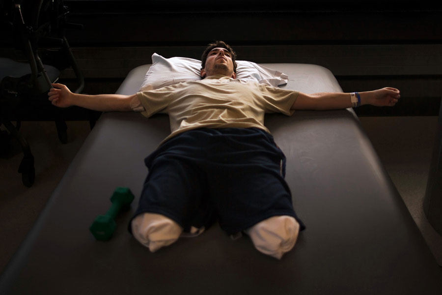 Jeff Bauman rests during occupational therapy at Spaulding Rehabilitation Hospital less than a month after having his lower legs blown off in the first of two pressure cooker bombs that exploded at the Boston Marathon. (Josh Haner, The New York Times - May 8, 2013)