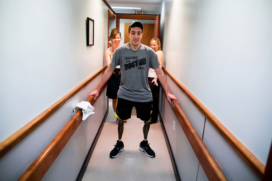 At a final fitting for his prosthetic legs, Bauman walked on his own for the first time since the day of the marathon. His girlfriend Erin, looked at him and said, 'I love that you're standing right now,' before coming around to steady him and kiss him. (Josh Haner, The New York Times - May 31, 2013)