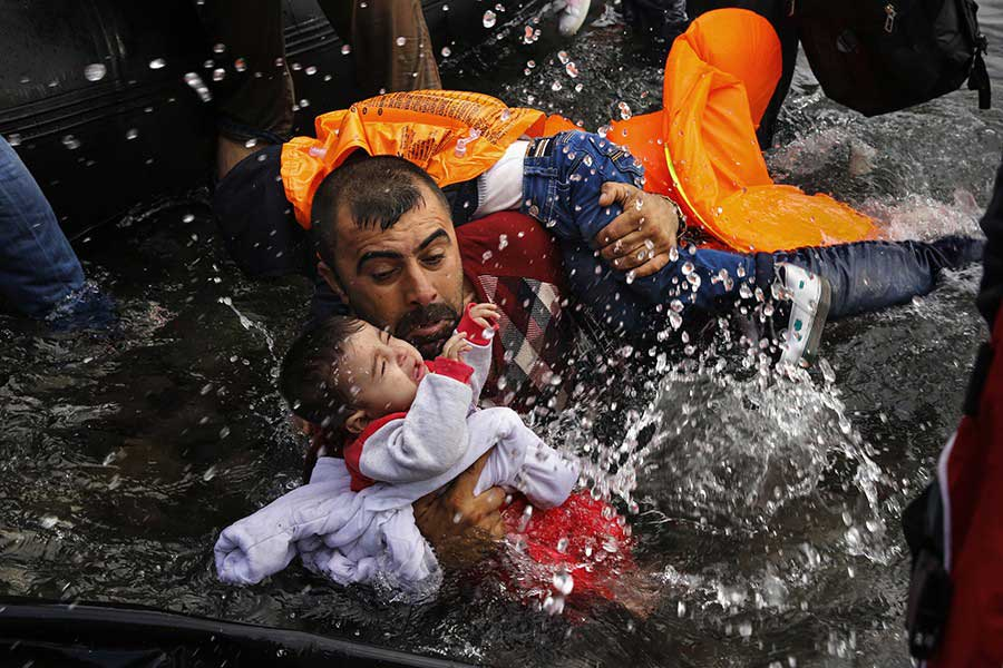A Syrian refugee holds onto his children as he struggles to walk off a dinghy on the Greek island of Lesbos / Yannis Behrakis, Thomson Reuters - September 24, 2015