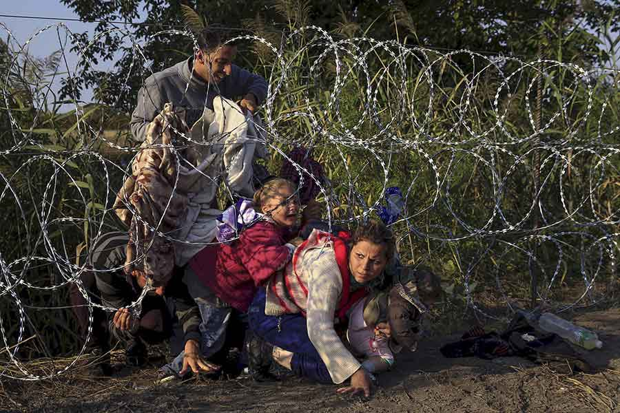 Syrian migrants cross under a fence as they enter Hungary at the border with Serbia / Bernadett Szabo, Thomson Reuters - August 27, 2015