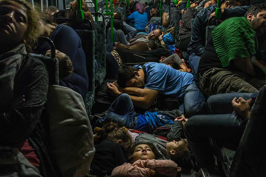 Ahmad Majid, in blue T-shirt at center, sleeps on a bus floor with his children, his brother Farid Majid, in green sweater at right, and other members of their family and dozens of other refugees, after leaving Budapest on the way to Vienna / Mauricio Lima, The New York Times - September 5, 2015