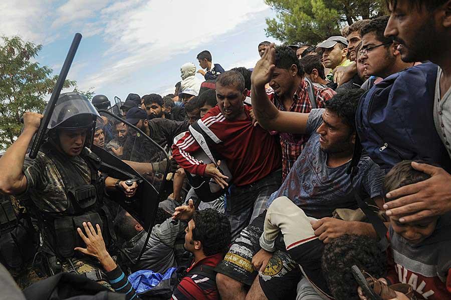 A Macedonian police officer raises his baton towards migrants to stop them from entering into Macedonia at Greece's border near the village of Idomeni / Alexandros Avramidis, Thomson Reuters - August 22, 2015