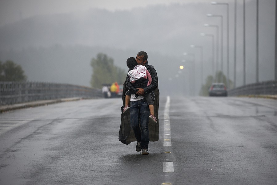 Syrian refugee kisses his daughter as he walks through a rainstorm towards Greece's border with Macedonia, near the Greek village of Idomeni / Yannis Behrakis, Thomson Reuters  - September 10, 2015