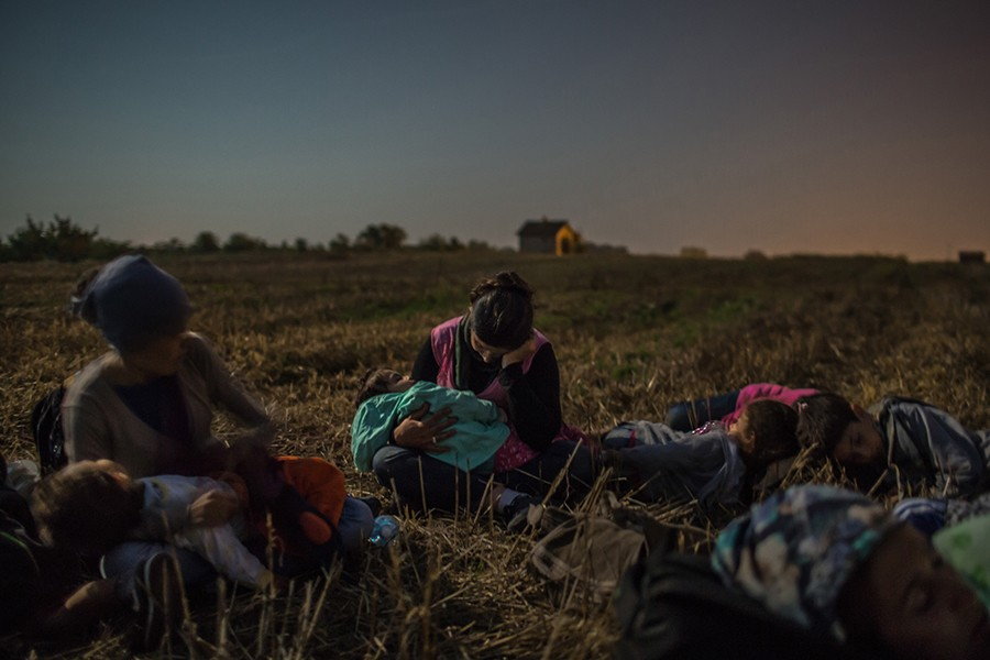 Members of the Majid family sleep with their children in their arms in a wheat field as they wait to cross the barbed wire fence at Horgos, Serbia, into Hungary / Mauricio Lima, The New York Times - August 31, 2015