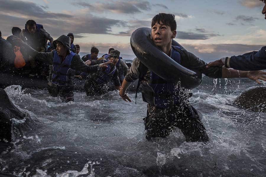Migrants arrive by rubber raft on a jagged shoreline of the Greek island of Lesbos / Tyler Hicks, The New York Times - October 1, 2015