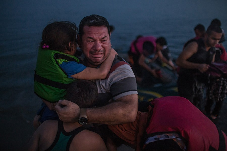 Laith Majid, an Iraqi, broke out in tears, holding his son and daughter after they arrived safely in Kos, Greece, on a flimsy rubber boat / Daniel Etter, The New York Times - August 15, 2015