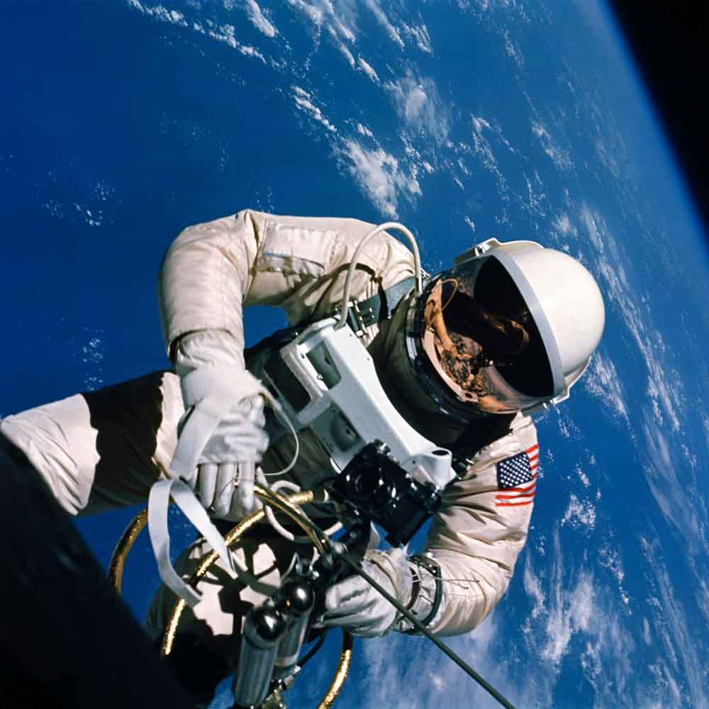 ASTRONAUT EDWARD H. WHITE FLOATING IN ZERO GRAVITY WITH EARTH BEHIND HIM, JUNE 1965 © NASA