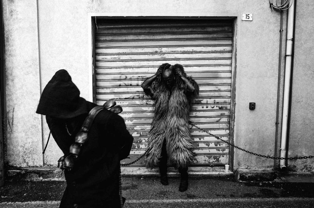 Due maschere e recitanti nel Carnevale sardo a Fonni (NU) davanti ad un negozio
