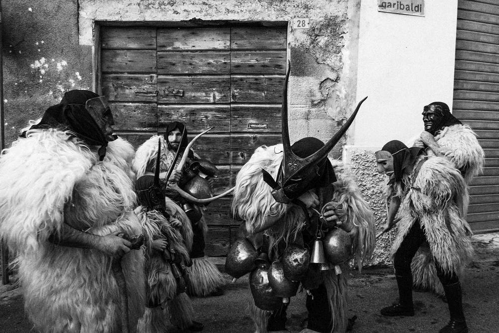 Figuranti mascherati da buoi e pastori in pelliccia si esibiscono per strada