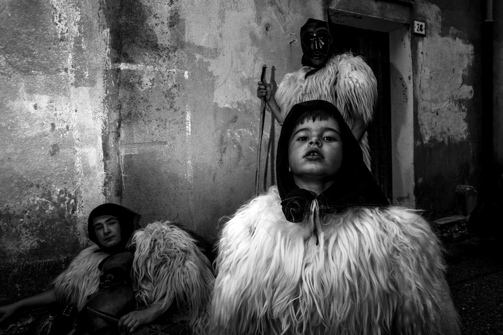 Adulti e bambino vestiti da pastori con pellicce sostano per strada a Ottana (NU)
