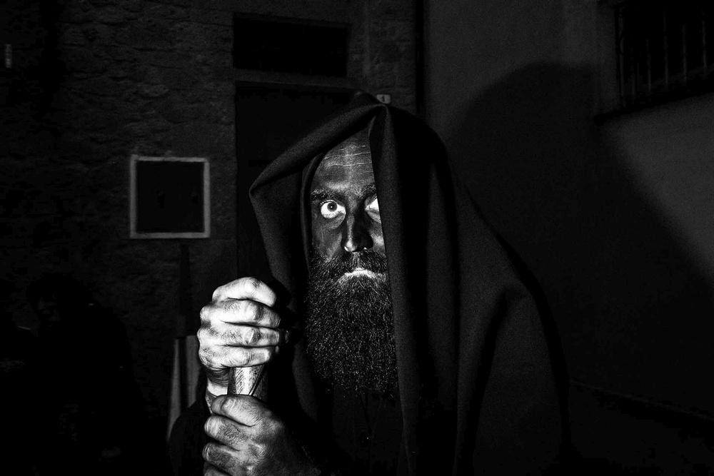 Un uomo con il volto coperto di fuliggine ed il bastone fissa da sotto una tunica
