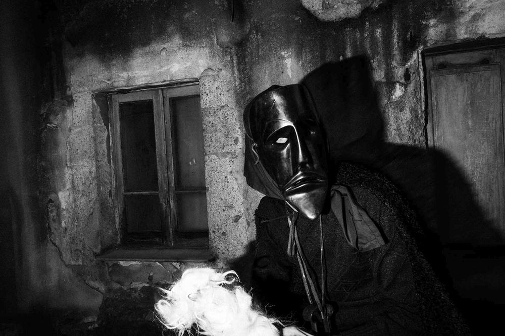In una casa dai muri anneriti una maschera scura è illuminata dal colpo del flash