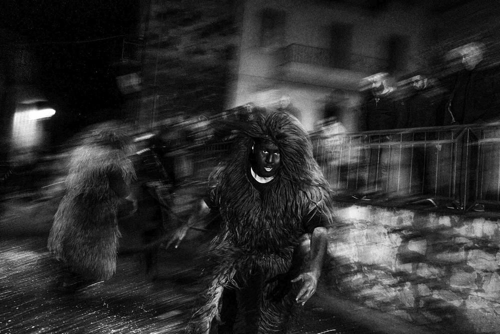Le maschere di Urthos e Buttudos sfilano per strada. Volti coperti di fuliggine e pelli di animali
