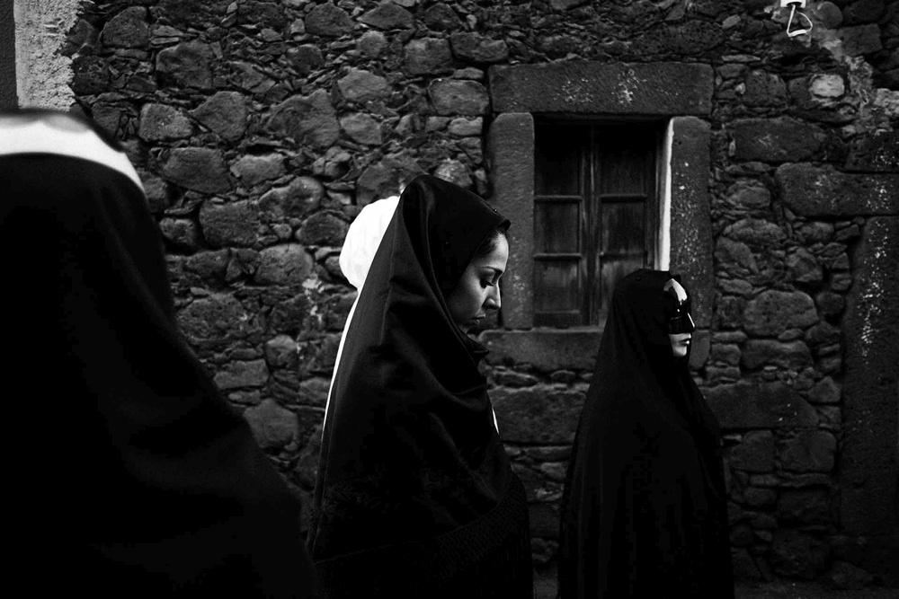 Donne e ragazze in maschera, realizzate con drappi e lenzuola, sfilano composte per strada