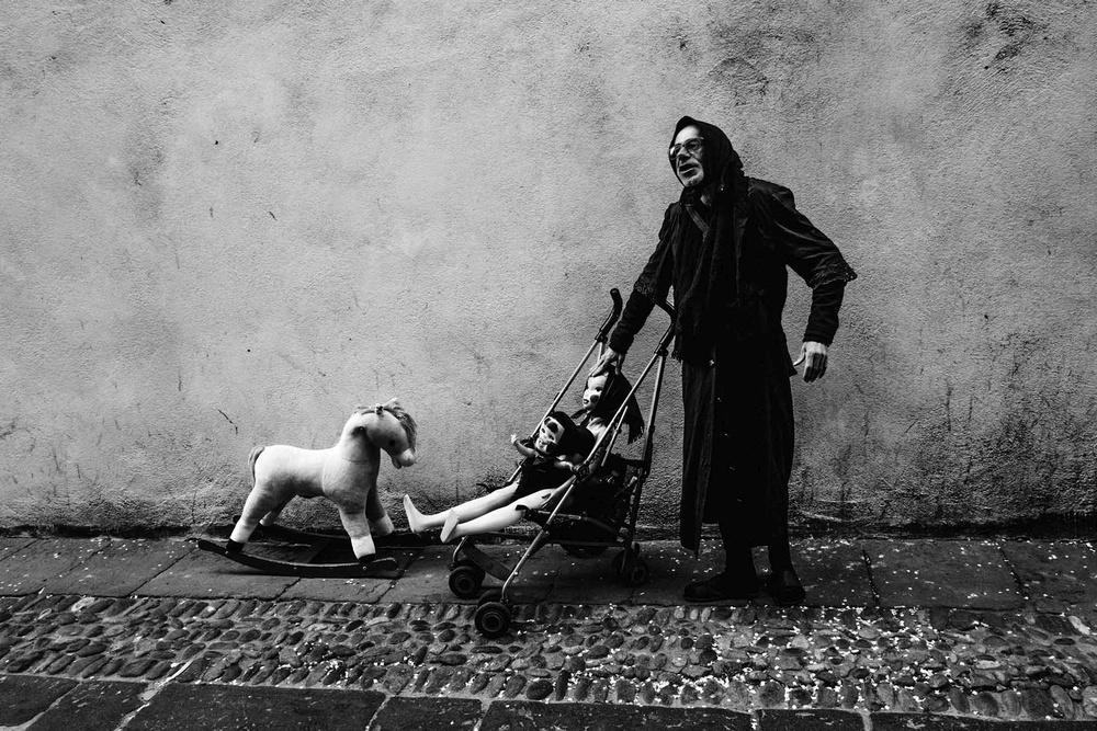 Una figura magra ed inquietante sfila per strada con giocattoli per bambini