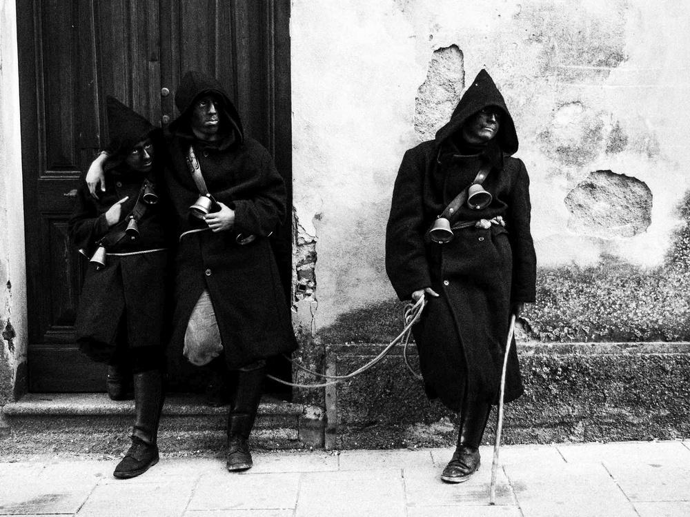 Tre uomini mascherati e incappucciati, addobbati con campanacci, sostano davanti ad una casa bianca ed al suo portone scuro