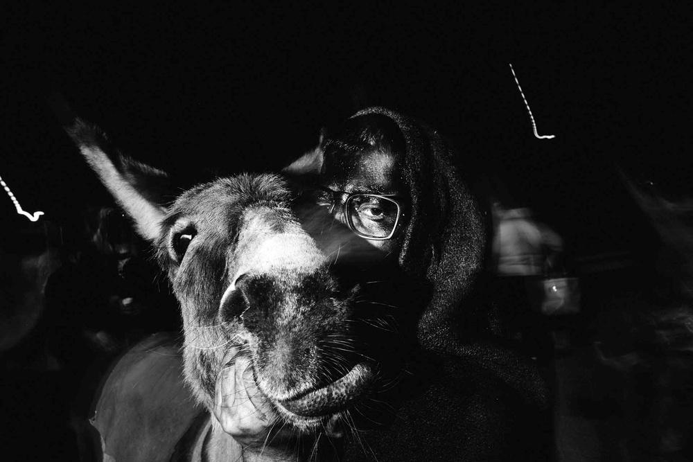 Merhuris de lessia: una figurante con il viso coperto di fuliggine ed il suo asino