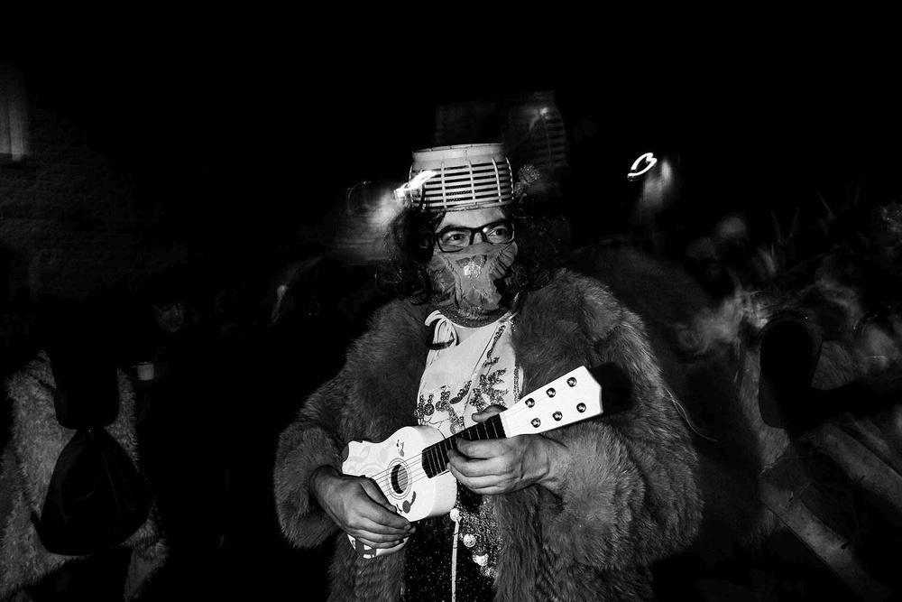 Un musicante vestito di pelliccia e mascherato suona l'ukulele per strada a Gavoi (NU)